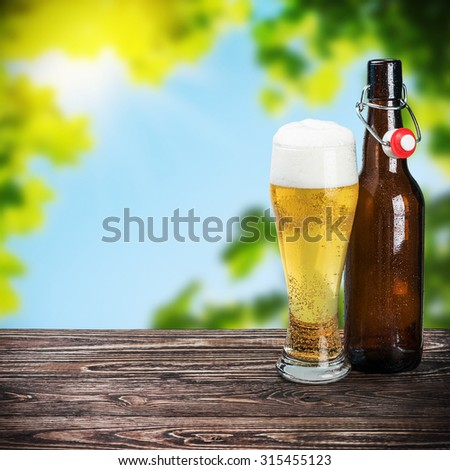glass of beer and an empty bottle on the table on nature background - stock photo