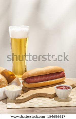 Glass of beer and hot dog with a cup of ketchup - stock photo