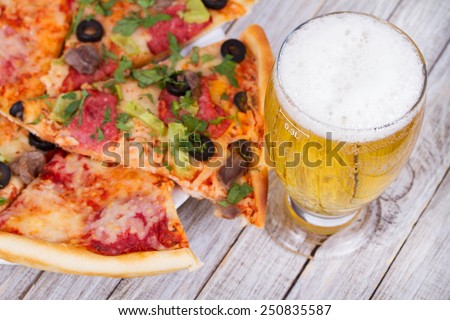 Glass of beer and pizza - stock photo