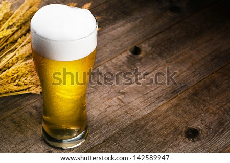 glass of beer and wheat on wooden table - stock photo
