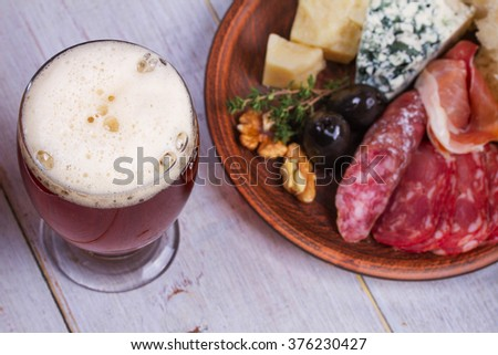 Glass of beer. Cheese,  prosciutto, salami, rosemary, nuts, olives and bread. View from above, top shot - stock photo