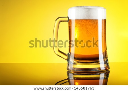 Glass of beer close-up with froth over yellow background - stock photo