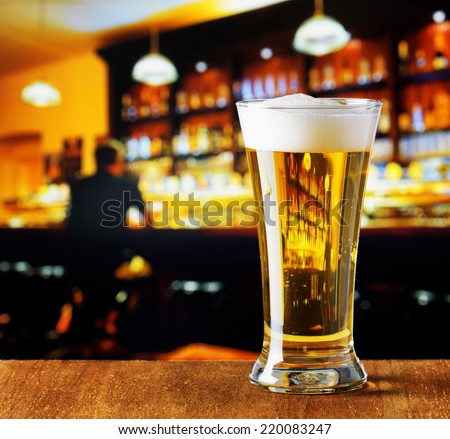 Glass of beer in a bar. - stock photo