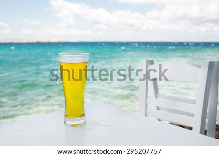 glass of beer on a table against the sea - stock photo