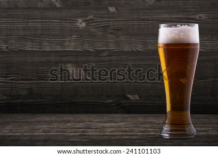 Glass of beer on a wooden countertop - stock photo