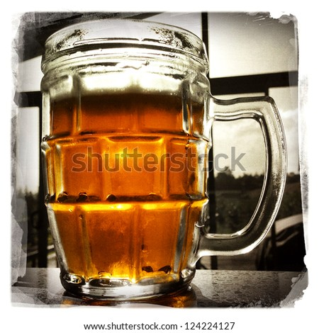 Glass of beer on counter top - stock photo