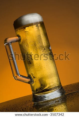 glass of beer on orange background close up - stock photo