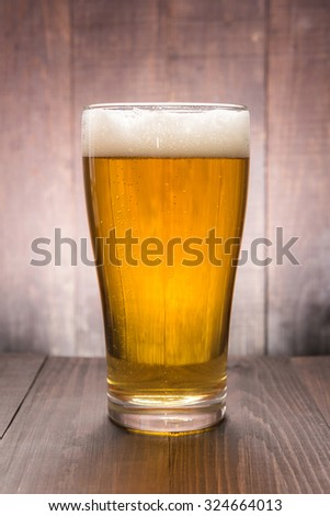 Glass of beer on the wooden background. - stock photo