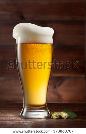 Glass of beer on wooden background with green hop - stock photo