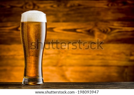 Glass of beer on woodend table and wooden background - stock photo