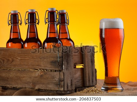 Glass of beer with bottles in crate and barley still life - stock photo