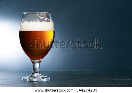 Glass of beer with foam on nice dark background - stock photo
