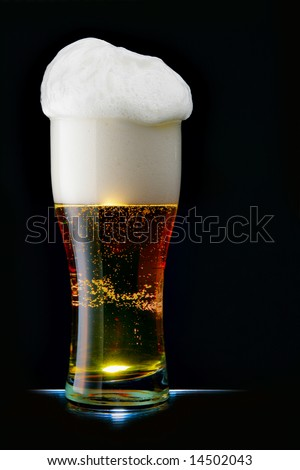 Glass of beer with froth over black background - stock photo