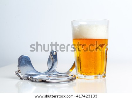 Glass of beer with handcuffs as symbol for alcohol abuse - stock photo