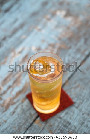 glass of beer with ice on wooden table, selective focus. - stock photo