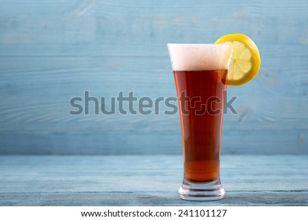 Glass of beer with lemon - stock photo