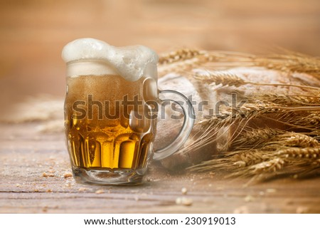 Glass of beer with wheat and bread on wooden background - stock photo