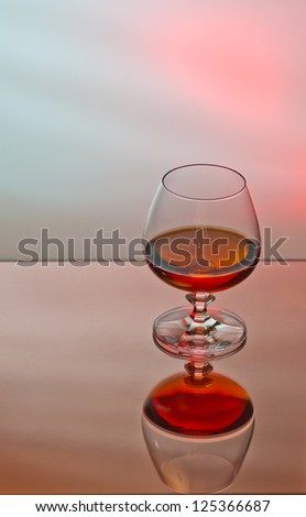 glass of brandy on moody background - stock photo