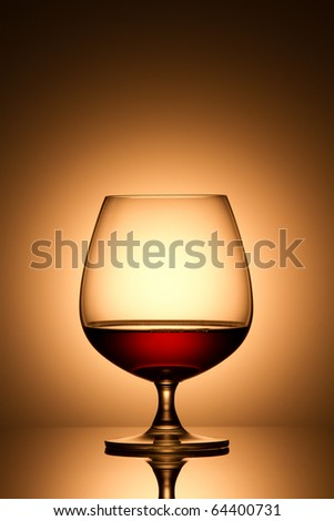 Glass of brandy over gold background - stock photo