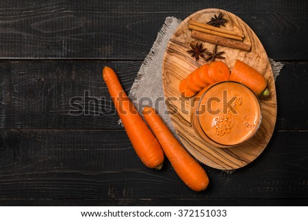 Glass of carrot juice and carrots on black wooden background, top view - stock photo