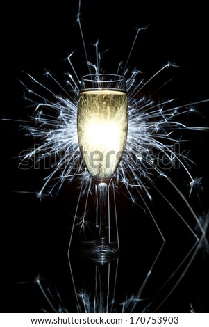 Glass of champagne and burning sparkler - stock photo