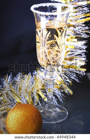 Glass of champagne and streamers on black table - stock photo