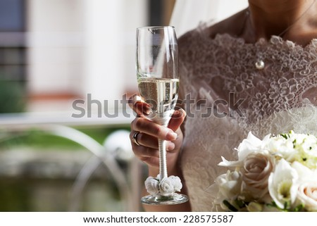 Glass of champagne in a hand of the bride  - stock photo