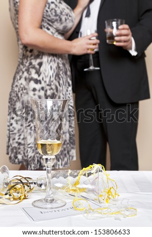 Glass of champagne on a table with an invitation and guests drinking in the background, focus is on the foreground. Good image for a Wedding, Party or New Year Eve theme. - stock photo