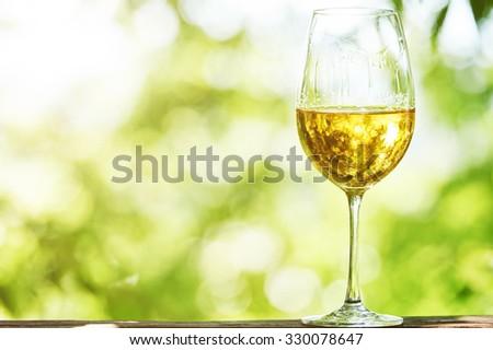 Glass of Chardonnay, Sauvignon or Rkatsiteli white wine over outdoors background  - stock photo