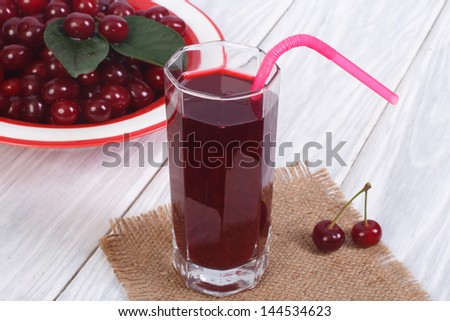 glass of cherry juice and plenty of ripe cherries on the table - stock photo