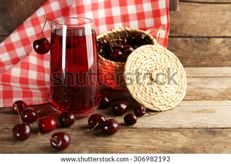 Glass of cherry juice on wooden table with checkered napkin on background - stock photo