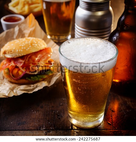 Glass of chilled beer served with a cheeseburger and French fries for a relaxing lunch in a pub or bar - stock photo