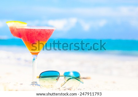glass of chilled cocktail rum punch and sunglasses on table near the beach - stock photo