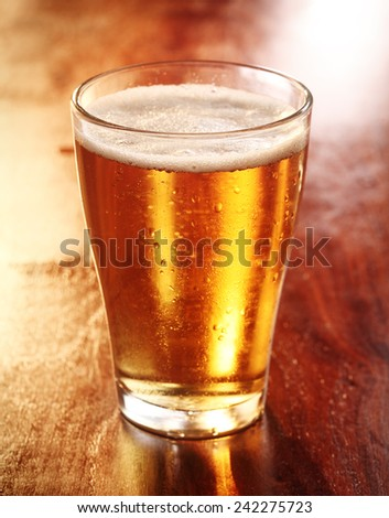 Glass of chilled glowing golden backlit lager or beer standing on a wooden counter in a tavern, pub or bar - stock photo