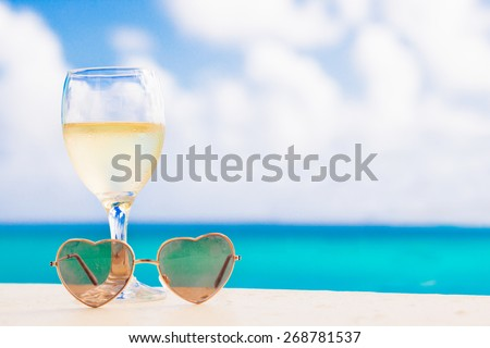 glass of chilled white wine on table near the beach - stock photo