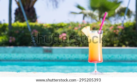 Glass of Cinderella kids cocktail on the pool nosing at the tropical resort. Horizontal, wide screen - stock photo