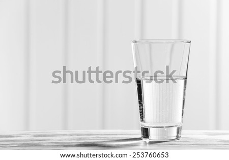 Glass of clean mineral water on old color wooden surface and planks background - stock photo