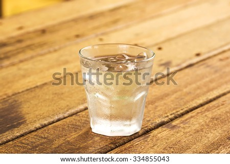glass of clear alcohol on wooden table - stock photo
