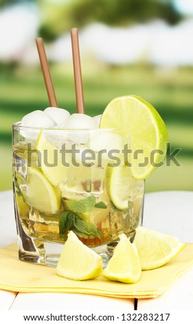 Glass of cocktail with lime and mint on white wooden table on bright background - stock photo