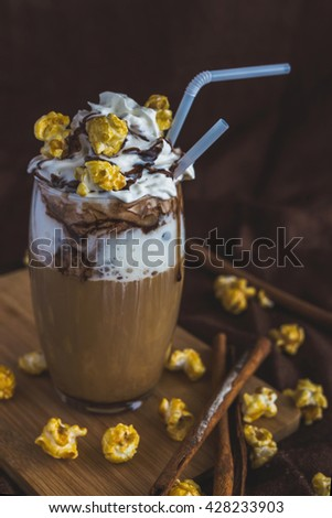 Glass of coffee latte with whipped sour cream, caramel popcorn, cinnamon  and chocolate - stock photo