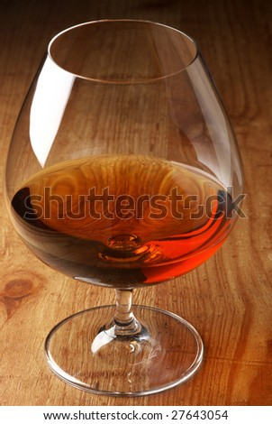 Glass of cognac close-up on wood background. - stock photo