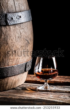 Glass of cognac in the old cellar - stock photo
