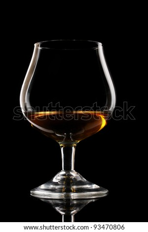 Glass of cognac on black background - stock photo