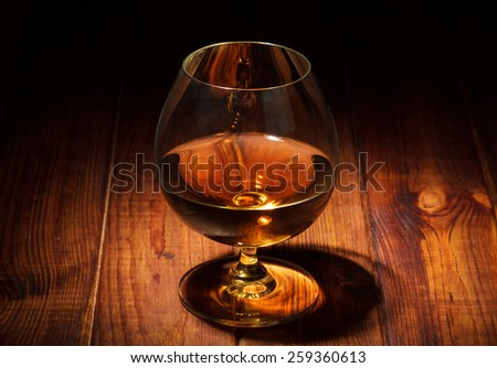 Glass of cognac on wooden background - stock photo