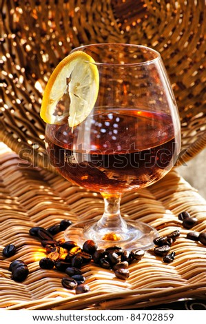 Glass of cognac with lemon and coffee beans - stock photo