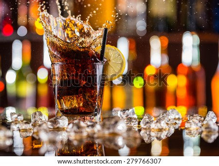 Glass of cola drink on bar counter with ice cubes and splash - stock photo