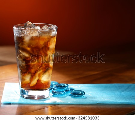 Glass of cola drink on brown background  - stock photo
