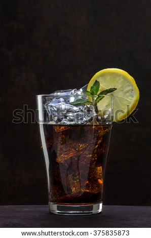 glass of cola or coke with ice cubes, lemon slice and peppermint garnish on a wooden table against a dark brown wall, copy space, selected focus, vertical - stock photo