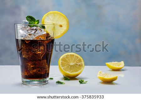 glass of cola or ice tea with ice cubes, lemon slice and peppermint garnish, against a blue wall - stock photo