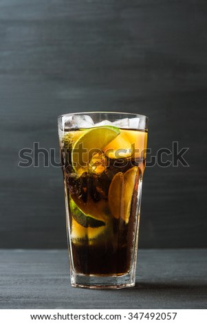 Glass of cola with ice and lime on the rustic background - stock photo